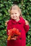 Autumn Portrait Criança de sorriso que guarda o ramalhete das folhas de outono Imagens de Stock