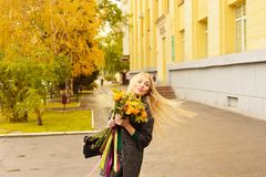 Autumn portrait of cute blonde girl. Portrait of a young girl in a lovely autumn day, with a bouquet of yellow and orange with satin colored ribbons Royalty Free Stock Photo