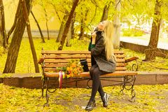 Autumn portrait of cute blonde girl. Portrait of a young girl in a lovely autumn day, with a bouquet of yellow and orange with satin colored ribbons Stock Photography