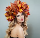 Autumn portrait of cute blonde woman. Pretty model with autumn leaves, makeup and long curly hair.  stock photos