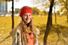 Autumn portrait of a cute girl in a red hat and coat with a scarf stock photos