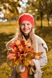 Autumn portrait of cute girl in red hat and coat stock image