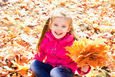 Autumn portrait of cute happy little girl with maple leaves Royalty Free Stock Photography