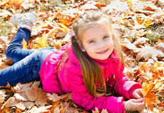 Autumn portrait of cute little girl lying in maple leaves Royalty Free Stock Image