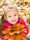 Autumn portrait of cute smiling little girl with maple leaves Royalty Free Stock Photo