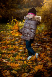 Autumn portrait of cute smiling little girl with maple leaves Stock Photos