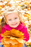 Autumn portrait of cute smiling little girl with maple leaves Royalty Free Stock Images