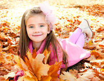 Autumn portrait of cute smiling little girl with maple leaves Stock Photography