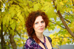 Autumn Portrait Of A Girl. Portrait of a redheaded girl near a tree (autumn colors Royalty Free Stock Photography