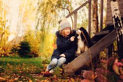 Autumn portrait of happy kid girl playing with her spaniel dog in the garden Royalty Free Stock Photography