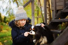 Autumn portrait of happy kid girl playing with her spaniel dog in the garden Stock Photos