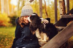 Autumn portrait of happy kid girl playing with her spaniel dog in the garden Royalty Free Stock Images