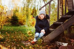 Autumn portrait of happy kid girl sitting in garden Royalty Free Stock Images