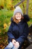 Autumn portrait of happy kid girl sitting in garden Stock Photos