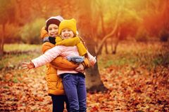 Autumn portrait of happy kids playing outdoor in park. Smiling brother and sister walking in sunny day, wearing warm knitted hats and scarfs royalty free stock photo