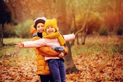 Autumn portrait of happy kids, brother and sister. Autumn portrait of happy kids playing outdoor in park. Smiling brother and sister walking in sunny day stock photos