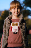 Autumn portrait. Of a little blond girl in fur waistcoat  in a park Stock Photo