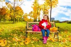 Autumn portrait of little girl on the bench Stock Photo