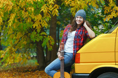 Autumn portrait of pretty guitarist girl travelling by yellow minibus Stock Photography