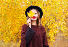 Autumn portrait pretty smiling woman wearing a black hat and knitted poncho over sunny yellow leaves. Background Royalty Free Stock Photography