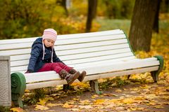 Autumn portrait of sad lonely child girl sitting on bench in park in warm blue coat and hat,enjoying outdoor walk in royalty free stock images