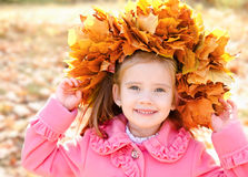 Autumn portrait of smiling little girl in maple wreath Royalty Free Stock Image