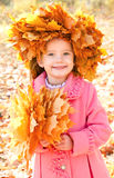 Autumn portrait of smiling little girl in maple wreath Stock Photos