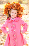 Autumn portrait of smiling little girl in maple wreath Stock Image