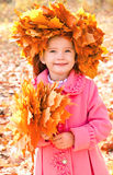 Autumn portrait of smiling little girl in maple wreath Royalty Free Stock Photos