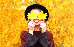 Autumn portrait smiling woman hides her eyes maple yellow leaves Royalty Free Stock Photography