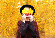 Autumn portrait smiling woman wearing a black hat and knitted poncho over sunny yellow leaves. Background Royalty Free Stock Photo