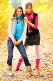 Two girls posing and smiling in autumn forest. Portrait of a young girl standing together Stock Photography