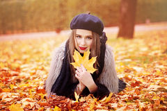 Autumn Portrait of Woman Fashion Model with an Fall Maple Leaf Stock Photography
