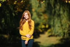 Autumn portrait of a young beautiful redhead woman in yellow sweater with a noon sun and shallow depth of field Royalty Free Stock Image