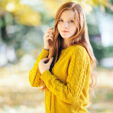 Autumn portrait of a young cute redhead woman in yellow sweater. Autumn portrait of a young beautiful redhead woman in yellow sweater Stock Image
