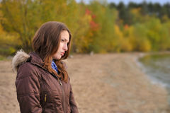 Autumn portrait of a young girl. Young girl standing near the water of lake in autumn park Stock Photos