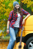 Autumn portrait of young guitarist woman at yellow minibus and autumn dry yellow leaves background Stock Photography