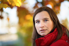 Autumn portrait. Young woman in a red jacket on a background of autumn leaves close-up. Bright colorful bokeh. Shallow depth of field. Selective focus on the stock image