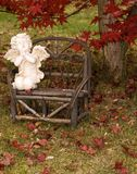 Autumn Prayer. Lawn figurine placed on wooden bent wood bench displayed under a Japanese Maple tree in autumn Stock Image