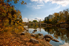Autumn at Prince's Island Park. Autumn park landscape with bridge, pond and leaves on the ground Royalty Free Stock Photography