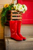 Autumn. Spring.Protection in the rain. red rubber boots on stairs. Street, house entrance. Raindrops. Copy space royalty free stock images