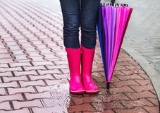 Autumn. Protection in the rain. Woman (girl) wearing pink rubber boots and has colorful umbrella. royalty free stock photos