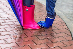 Autumn. Protection in the rain. Woman wearing pink rubber boots with umbrella and her child having fun in the rainy day. stock photos