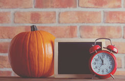 Autumn pumpkin and blackboard menu with alarm clock. On wooden table with brick wall at background Royalty Free Stock Photo