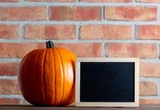 Autumn pumpkin and blackboard menu Royalty Free Stock Photography