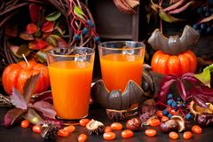 Autumn pumpkin cocktail with Halloween decor on dark backgroun royalty free stock photo