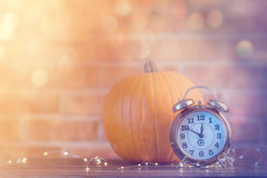 Autumn pumpkin with Fairy Lights and alarm clock Stock Photo