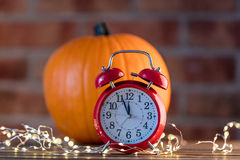 Autumn pumpkin with Fairy Lights and alarm clock Royalty Free Stock Image