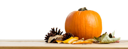 Autumn Pumpkin and Leaves. A banner style still life a pumpkin. Autumn leaves and fir cones on a wooden table, isolated against a white background Royalty Free Stock Images