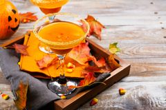 Autumn pumpkin martini cocktail with fall leaves on wooden tray royalty free stock photography